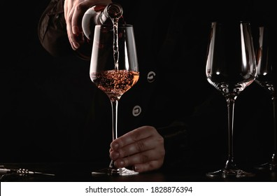 Sommelier pouring rose wine into glass at wine tasting in winery, bar or restaurant. Dark background