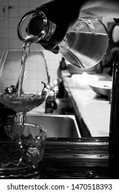 Sommelier pouring white wine in glasses from decanter at the luxury restaurant. Sommelier holding decanter with wine.