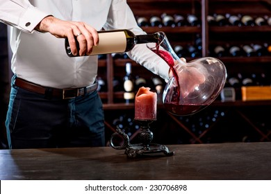Sommelier pouring wine to the decanter in the wine cellar