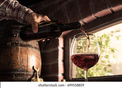 Sommelier pouring wine into a balloon glass in the cellar: wine tasting and traditional winemaking concept