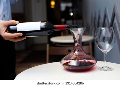sommelier is pouring wine into a decanter