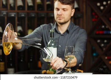Sommelier pours white wine from decanter to the glass