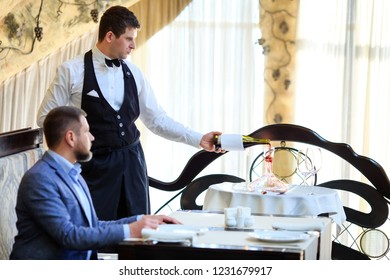 The sommelier pours the wine into the decanter near the guest in the restaurant.