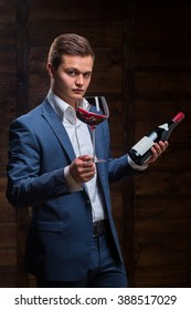 Sommelier in suite looking at red wine. Caucasian businessman looking at the Glass of Red Wine. Confident oligarch looks at a glass of a red wine