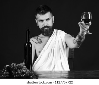 Sommelier tastes drink. Man with beard holds glass of wine on brown background. Winemaking and degustation concept. God Bacchus with smile on face wearing white cloth sits by wine bottle and grapes.
