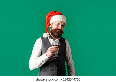 Sommelier tasting red wine. Man in waistcoat drink glass of red wine. Santa man tasting glass of wine. Winetasting and degustation. New year party. Christmas. Bearded man in Santa hat drinks red wine.