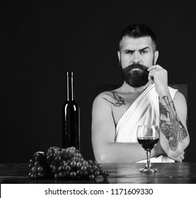Sommelier tasting wine. Man with beard near glass of alcohol on brown background. God Bacchus with strict face wearing white cloth sits by wine bottle and grapes. Viticulture and grape harvest concept