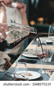 sommelier at wine tasting pouring red wine from decanter into glass at wine tasting