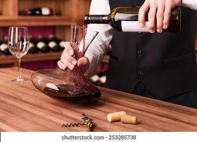 Sommelier at work. Confident male sommelier pouring wine to decanter while standing near the wine shelf