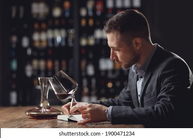 Sommeliers male hold glass red wine tasting and making notes degustation card.