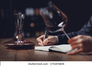 Sommeliers male tasting red wine and making notes aroma degustation card.