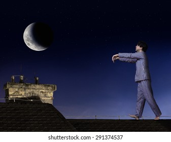Somnambulist walking on the roof. Man in pajamas walks on roof with outstretched hands. Moony in pajamas walks at night on roof of a house under moonlight. Sleepwalker walk under the moon.