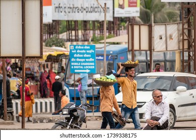 Somnath, Gujarat, India - December 2018: Two street vendors smiling and walking on a crowded market street carrying a basket of fruits on their heads.