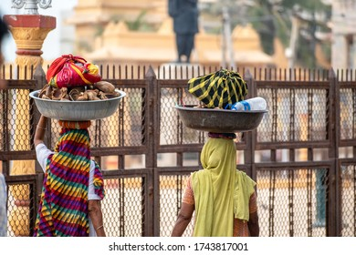 Somnath, Gujarat, India - December 2018: Two Indian women walk on the street carrying food and water on their heads.