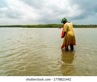 Somone, Senegal- July 18 2020: Senegalese woman collecting mussel and clam, most important income resource for local people.