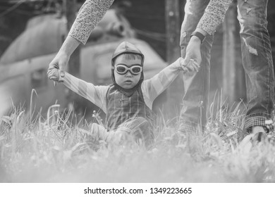 Son baby in pilot helmet and glasses holding hands with mother in green grass on blurred helicopter. Playing and dreaming. Travelling and adventure. Happy childhood and mothers day concept.