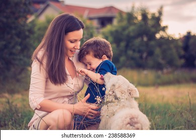Son being licked by a dog while in mothers arms