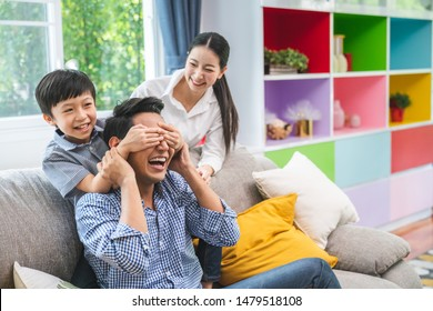 Son blindfolded cute father at home and kids laughing spending time together enjoying on weekend, happy family with father , mother and sons having fun leisure activity in living room
