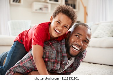 Son Climbs On Fathers Back As They Play Game In Lounge Together