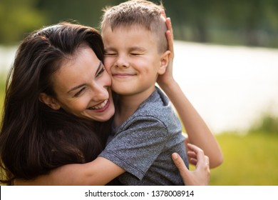 Son with closed eyes hugging his mother tightly