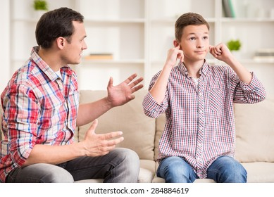 Son closing ears while father scolding  him.
