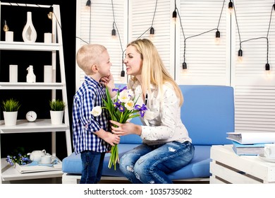 Son congratulates his beloved mother and gives her a bouquet of tulips.The concept of the celebration,women's day.Mother's Day.