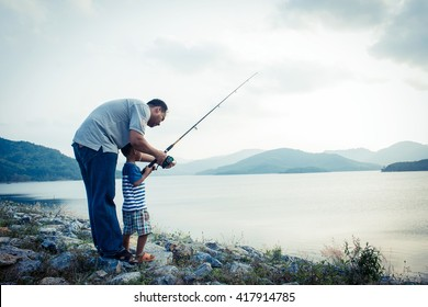 son and dad fishing at dam,vintage tone