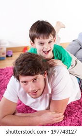 Son and dad having fun on the floor