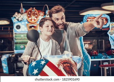 Son and Dad are having fun while riding a motorcycle. Dad helps his son drive a motorcycle on a slot machine and smiles.