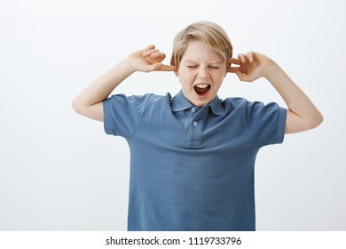 Son do not want to be obedient, making noise and misbehave. Portrait of displeased unhappy child standing over gray background, yelling and whining while covering ears with index fingers