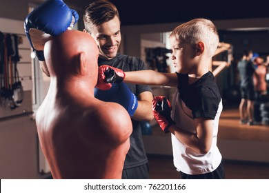 Son and father is doing sports in the gym. They leads a healthy lifestyle. A man and boy is boxing a mannequin. Body opponent bag and son in boxing gloves.