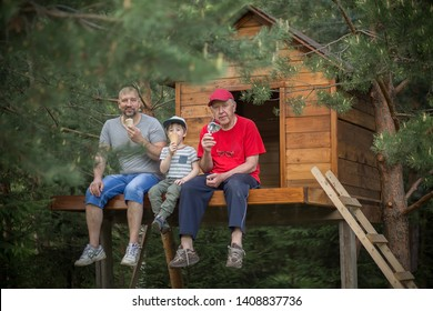 A son, father and grandfather are eating ice-cream together sitting in the tree house. Image with selective focus and toning