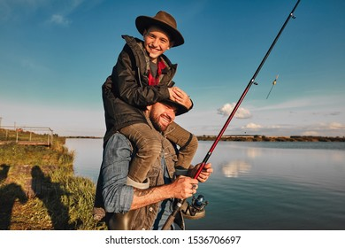 Son and father have fun while fishing. Father holds son on shoulders. Boy hold head. They smile. Background lake.