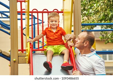 son and father at a playground. playing family outdoors