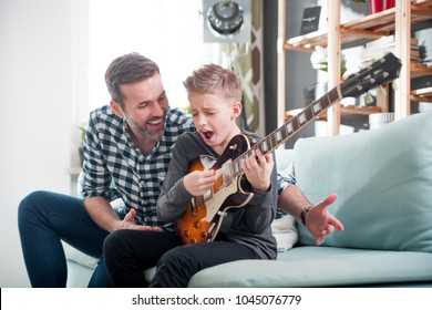 Son and father playing electric guitar on sofa at home