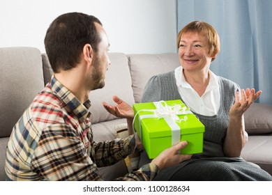 Son gives holiday gift box to elderly mother at home