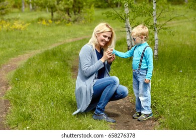 son giving flowers to his mother. child and mom walking