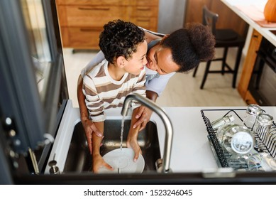 Son is helping mother in the Kitchen, Washing Dishes. African American family.