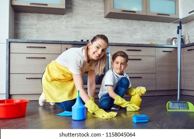 Son helps mom clean up in the kitchen.