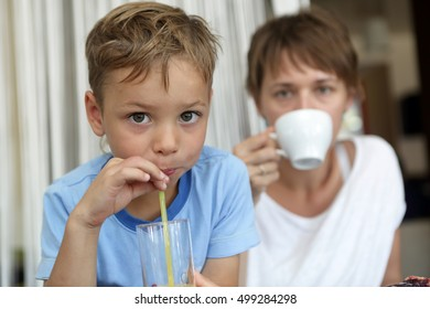 Son and his mother drinking beverages in cafe