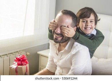 Son holding eyes of father with gift at Father's Day