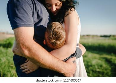 Der Sohn umarmte Eltern mit der Natur. Mama, Papa und Junge gehen im Gras spazieren. Fröhliche junge Familie verbringt Zeit zusammen, draußen, im Urlaub, im Freien. Das Konzept des Familienurlaubs.