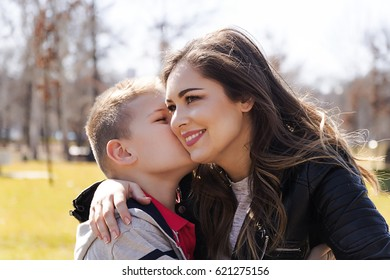 The son kisses and hugs his mom outdoors. Mother and her child having fun together. Little kid express the love to his young mommy.