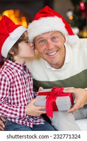 Son kissing his father after receiving a christmas gift at home in the living room