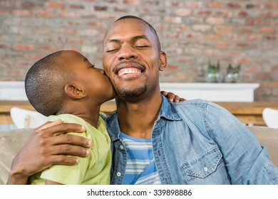 Son kissing his father on the couch in living room