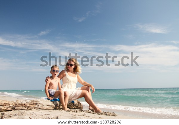 son kissing mom, they sit on the beach, past the boat floats