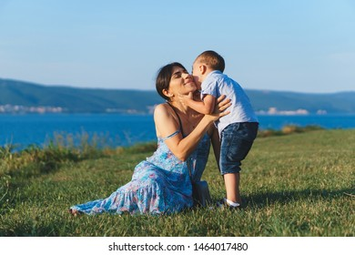 son kissing mother on green meadow in sunlight