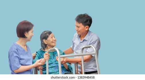 Son looking after elderly mother on wheelchair with caregiver