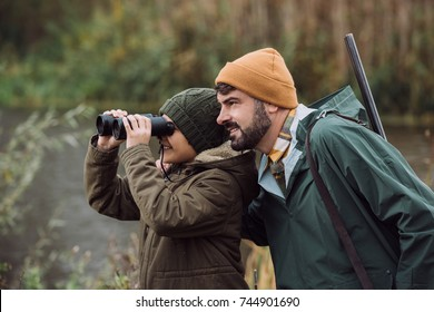 Son looking through binoculars, father standing with a gun
