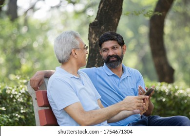 Son with old father talking at public park